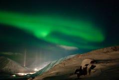 Ciudad, montañas y estrella polar de la aurora Imagen de archivo