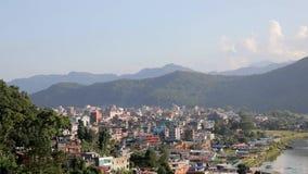 Ciudad por el lago en un valle de la montaña con una noria de la atracción, visión aérea de Pokhara metrajes
