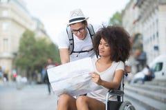 Ciudad que visita una de los pares en la silla de ruedas Foto de archivo