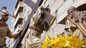 CIUDAD REAL SPANIEN - APRIL 14, 2017: Passera av bärande skulpturer av Jesus arg och roman soldat med ett spjut under dagproce lager videofilmer