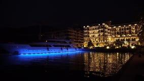 Ciudad Tivat de la noche en Oporto Montenegro Los barcos del hotel y de navegación en el Boka aúllan, Montenegro, Adriático, sept
