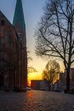 Ciudad vieja con las calles cobbled y una iglesia en Europa en la puesta del sol Imagen de archivo