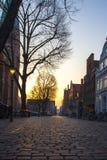 Ciudad vieja con las calles y los árboles cobbled en Europa en la puesta del sol Imagen de archivo