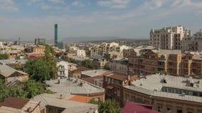 Ciudad vieja Georgia de Tbilisi de la pieza del panorama con los tejados de teja de la porción y las construcciones modernas, ras almacen de metraje de vídeo