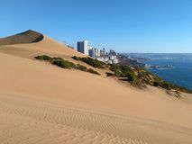 Ciudad y océano detrás de las dunas de arena fotos de archivo libres de regalías