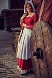 Ciudadana en vestido rojo con un delantal y señora de compañía en la calle fotos de archivo