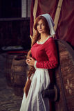 Ciudadana en vestido rojo con un delantal y señora de compañía en la calle fotografía de archivo libre de regalías