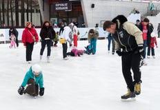 Ciudadanos que descansan sobre pista de hielo del invierno Imagenes de archivo