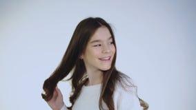 Civetta abbastanza giovane che tocca i suoi capelli e che flirta alla macchina fotografica stock footage