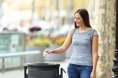 Civic woman throwing a paper into a trash bin royalty free stock image