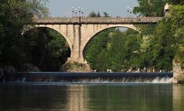 Cividale del Friuli/Itália - 25 de abril de 2018: A ponte do ` s do diabo no rio de Natison com alguns povos aprecia o sol sob el Imagens de Stock