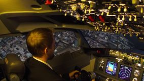 Civil aircraft cockpit. Pilot of passenger aircraft at work. Approaching stock video