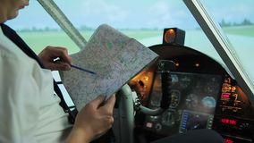 Civil aviation pilot preparing for departure, checking flight destination on map. Stock footage stock video footage
