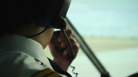 Civil aviation pilot using radio for communication with air traffic controller. Stock footage stock video footage