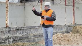 Civil engineer with cell phone near the unfinished building stock footage