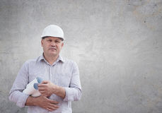 Civil engineer with construction plans. An engineer standing against gray wall holding construction plans in hands Royalty Free Stock Photo