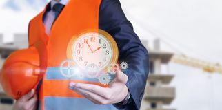Civil engineer displays the clock with gears. The concept of the efficient mechanism of implementation of the project Stock Photos