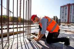 Civil engineer dressed in shirt, orange work vest and helmet measures the hole with a tape measure on the building site royalty free stock photography