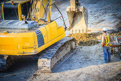 Civil engineer foreman is supervising backhoe to digging for ear. Thwork in highway construction site royalty free stock photo