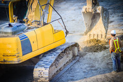 Civil engineer foreman is supervising backhoe to digging for ear. Thwork in highway construction site royalty free stock images