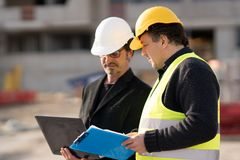 Foreman at work with a construction worker. Civil engineer giving instructions to a construction worker using a computer laptop. Outdoors Stock Photos