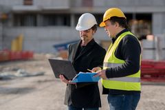 Foreman at work with one of the construction workers. Civil engineer giving instructions to a construction worker using a computer laptop. Outdoors Royalty Free Stock Images