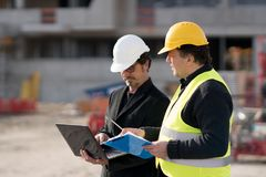 Construction manager and engineer at work on construction site. Civil engineer giving instructions to a construction worker using a computer laptop. Outdoors Stock Image
