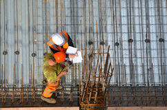 Civil engineer inspecting the work progress of a worker in a con Royalty Free Stock Photo