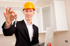 Civil engineer with a laptop gives the keys Stock Photo