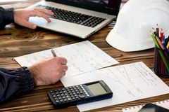 Civil Engineer making Structural Analysis Calculations. Civil Design Engineer is making structural analysis calculations using a scientific calculator Stock Photography