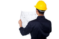 Civil engineer reviewing blueprint. Young male civil engineer reviewing construction site plan Stock Photos