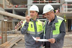 Civil Engineer and Senior Foreman At Construction Site. Are inspecting ongoing production according to design drawing royalty free stock images