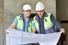 Civil Engineer And Senior Foreman At Construction Site. Are inspecting ongoing production according to design drawings stock images