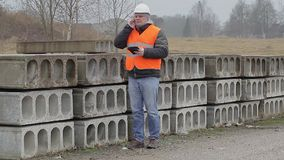 Civil engineer talking on cell phone near construction panels stock footage