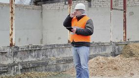 Civil engineer talking on cell phone near unfinished building stock video