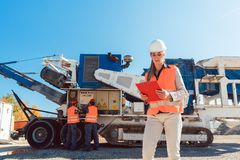 Civil Engineer woman with clipboard in front of stone crusher Royalty Free Stock Image