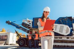 Civil Engineer woman with clipboard in front of stone crusher stock photos