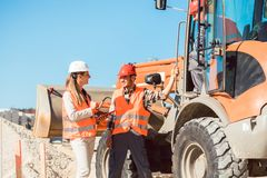 Civil engineer and worker discussion on road construction site. Women and man royalty free stock photo
