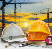 Civil engineer working table with safety helmet and writing inst. Rument against beautiful dusky sky and crane construction site Royalty Free Stock Image