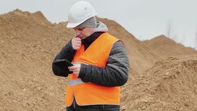 Civil engineer working with tablet PC at a pile of sand stock video footage