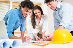 Civil engineers and architects talking about ground plot. For building Royalty Free Stock Image
