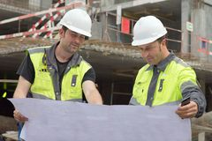 Civil Engineers At Construction Site. Are inspecting ongoing production according to design drawings stock photography