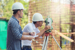 Civil Engineers At Construction Site and A land surveyor using a Stock Images