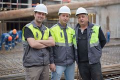 Civil Engineers At Construction Site. Two civil engineer and a senior foreman at construction site are inspecting ongoing construction works Royalty Free Stock Images