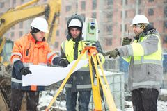 Civil engineers at construction site in winter season. Civil engineers at construction site are inspecting ongoing works according to design drawings in Stock Images