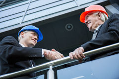 Civil engineers shaking hands. Close-up of civil engineers shaking hands on construction site stock image