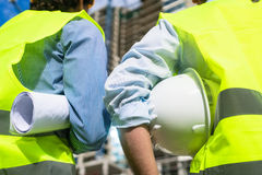 Civil engineers visiting building site. Civil engineers or architects visiting construction site, carrying plan and helmet royalty free stock photo