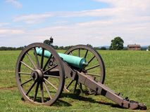 Civil war cannon with house and moument. Civil war cannon with house and man on a horse in the background royalty free stock photography