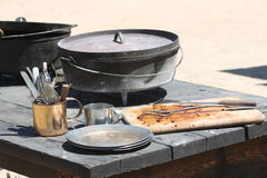 Civil War cookware. A collection of original pots, pans, plates and cutlery from the American civil war on top of an outdoor wooden table Stock Photography