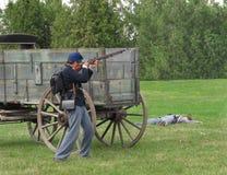 Civil War re-enactment soldier firing rifle. stock photos